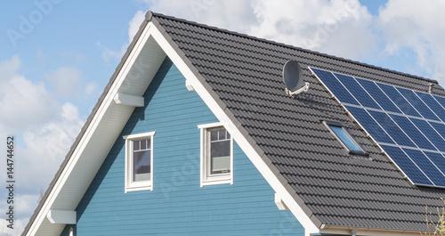 blaues haus mit solarzellen und fenstern im giebel zdj stockowych i obraz w royalty free w. Black Bedroom Furniture Sets. Home Design Ideas