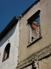 Einsturzgefährdeter Altbau mit ockerfarbener Fassade vor blauem Himmel in der Altstadt von Alacati in der Provinz Izmir in der Türkei