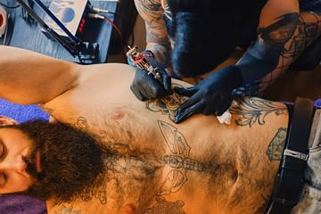 Female tattoo artist makes tattoo on bearded male torso in a salon.
