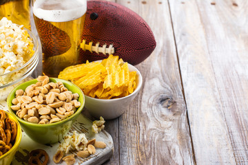 Beer, snacks and rugby ball on wooden table