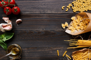 Dried mixed pasta and vegetables on the dark wooden table top view, with copy space