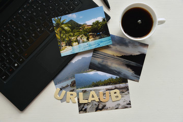 Urlaubsplanung online am PC Fotos Kaffee Laptop Büro