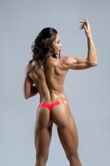 Female tanned bodybuilder posing topless in studio