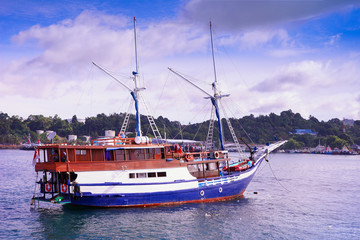 Indonesian wooden sailboat called pinisi, a  liveaboard ship for divers, or dive boat, near the island with the harbor.