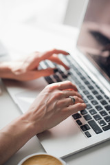 Close-up picture of woman's hands typing a message on her laptop during lunch.