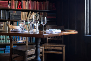 Foto op Aluminium Buffet, Bar Table set for two with wine glasses by window with books in the background. Intimate, private, cozy feeling.