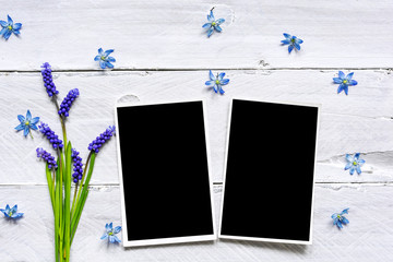blank photo frames and spring blue flowers bouquet