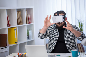 Man wearing virtual headset and exploring virtual world in office alone