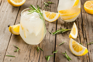 Summer refreshments. Detox water. Lemonade. Tonic with ice, lemon and rosemary, on an old wooden rustic table. Copy space