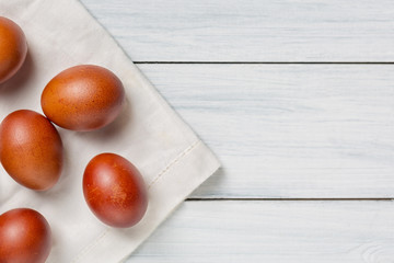 Colorful brown easter eggs on cloth and white wooden table with free space. Focus on eggs