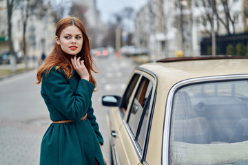 beautiful woman in a green coat stands near a car