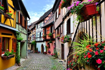 Fototapete - Quaint colorful cobblestone lane in the Alsatian town of Eguisheim, France