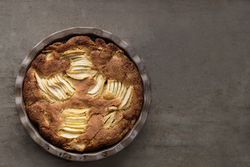 Apple, pear pie in ceramic pan from above. Dark food photography. Copy space for text