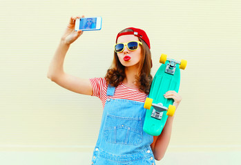Fashion pretty cool girl is taking picture self portrait on a smartphone over white background