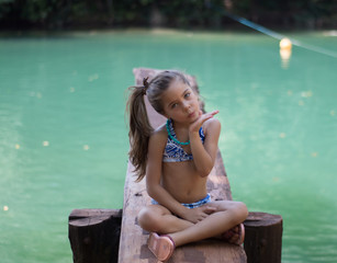 Cute little girl posing with lake background