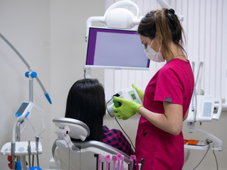 Dentist prepares to make tooth x-ray image for woman patient in dental clinic. Mobile portable x-ray device.