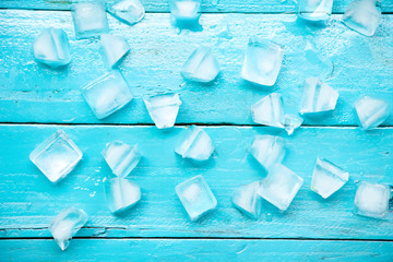 the cold ice cubes on blue wood background