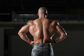 Muscular Man Flexing Back Muscles Pose
