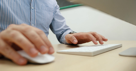 hands typing on computer keyboard in startup office