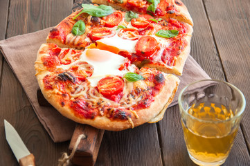 Homemade pizza with tomato sauce cheese egg and basil leaves served on board on wooden table. Top view