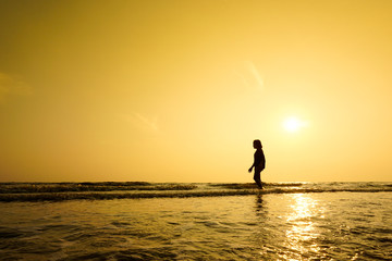 Silhouette of girl walking at the beach.