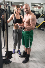 Man Exercising Biceps With Her Personal Trainer