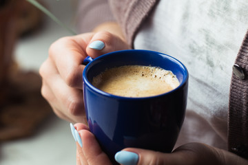 Girl with blue manicure holds a blue cup of coffee