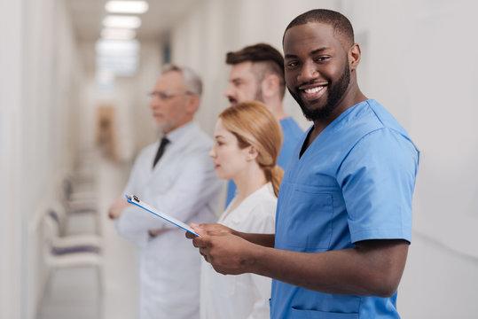 Joyful African American intern enjoying examination process in the clinic
