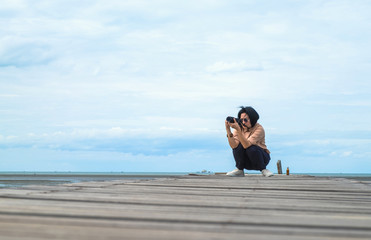 Asian woman traveler take photo of seascape on wood bridge with blue sky and ocean at background,low angel view