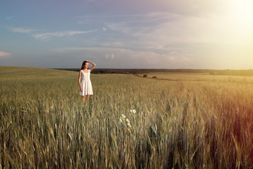 Beautiful young girl in summer field. Sky, sunlight, space