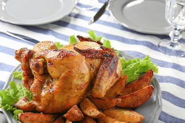 Plate with roasted beer can chicken on table