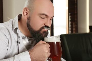 Bearded man drinking beer in pub