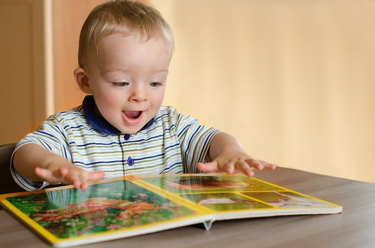 Baby boy is looking at animal book. Little toddler is excited by it. Child concept.