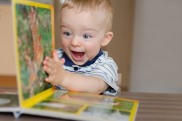Baby boy turns the page in the book with animal. He is very happy and excited by watching pictures. Child concept.