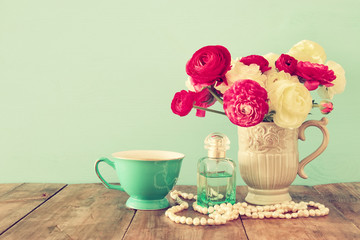 flowers in the vase next to cup of tea, pearls necklace and perfume bottle