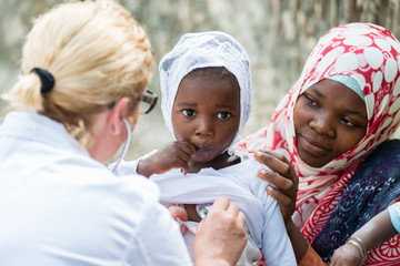 Female Caucasian doctor listening heart beat and breathing of little African girl with stethoscope.Mother holding the child