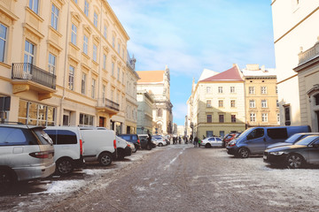 City street with old buildings and cars in winter