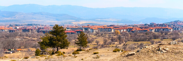 Bansko banner panorama with rows of hotels, tower and mountains at the background