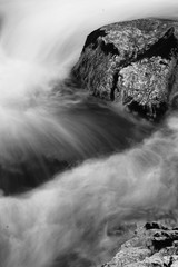rock in river brook in satin soft water flowing around in long exposure in black and white background