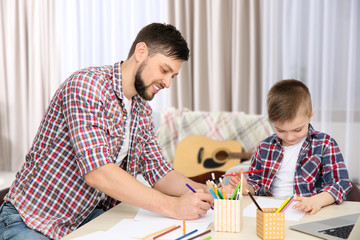 Father and his son drawing pictures at home