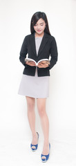 Smiling businesswoman standing over white isolated background reading book, office concept