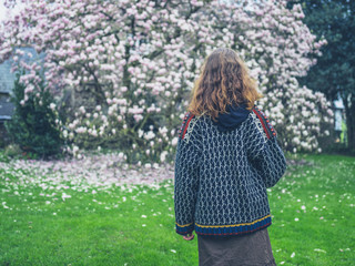 Young woman standing by magnolia tree in park
