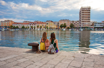 Two young girls with backpacks sitting on the stone pavement near the sea shore looking at the marine and pretty little colorful houses. Town of Zadar, Croatia