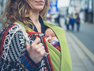 Mother with baby in carrier sling