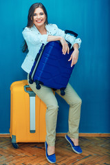 Happy woman sitting on suitcase.