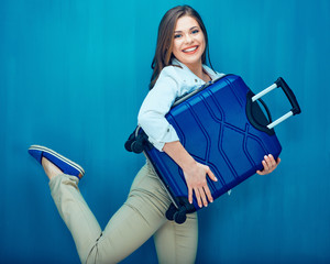 Happy young woman holding suitcase raise leg like a runner.