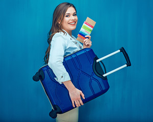 Woman traveler holding passport and suitcase.