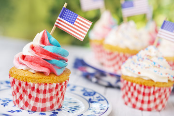 Cupcakes with red-white-and-blue frosting and American flags