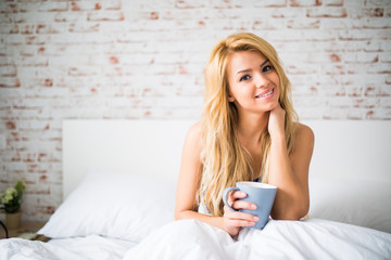 beauty young woman drinking cup of coffee or tea while lying in bed after waking up in morning.