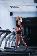 Vertical full length shot of a gorgeous young sportswoman with perfect strong toned body wearing sports top and shorts walking on a treadmill at the gym having her cardio workout at the health club .